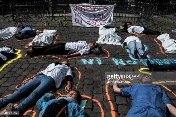 Employees of Lyon's hospitals emergency services take part in a 'diein' action on April 16 2018 in front the town hall in Lyon central eastern France...