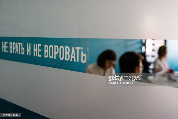 """Employees of Navalny's Anti-corruption Foundation work behind a glass door that reads """"Don't lie and don't steal"""" at their Moscow office on September..."""