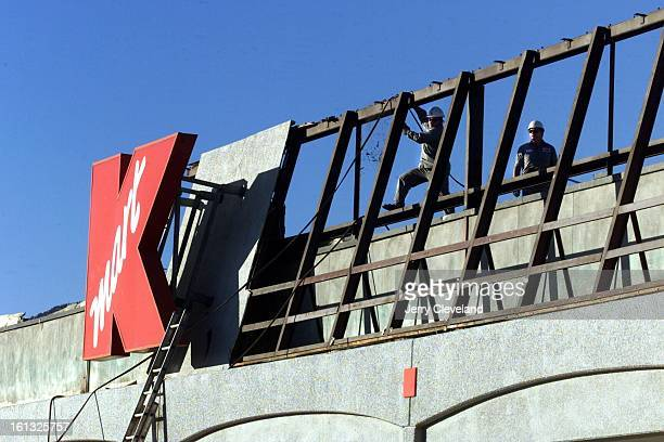 Employees of Penhall Company of Denver work at removing the sign from the former Kmart store at 28th Street and Iris Avenue in Boulder Tuesday...