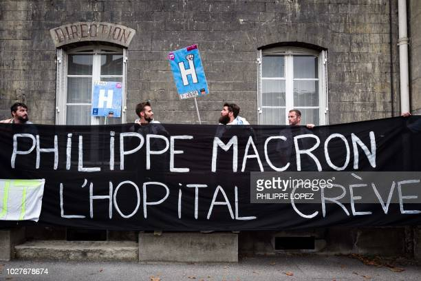 """Employees of psychiatric hospitals hold a banner reading """"Philippe Macron the hospital dies"""" as they protest against bad working conditions at the..."""