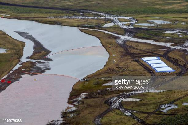 Employees of Russia's stateowned oil pipeline monopoly Transneft take part in a cleanup operation following a massive fuel spill in the Ambarnaya...