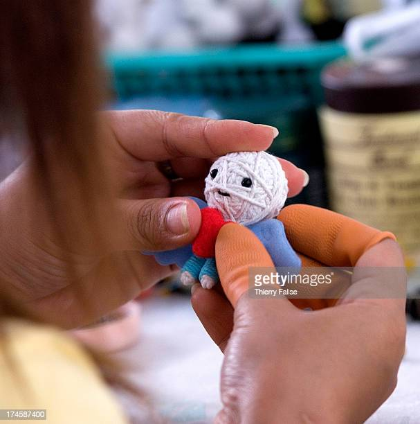 Employees of Sannha company put a final touch to voodoo dolls Saanha voodoo dolls are handmade with a single thread of cotton and miscellaneous...