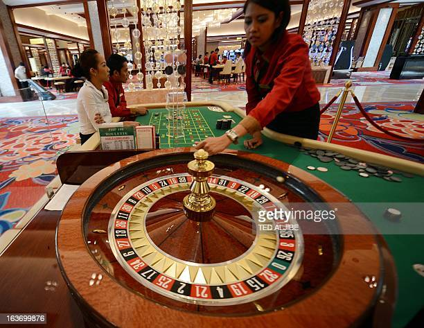Employees of Solaire Manila Resorts and casino simulate roulett game during media day inside the casino in Manila on March 14 ahead of its opening on...