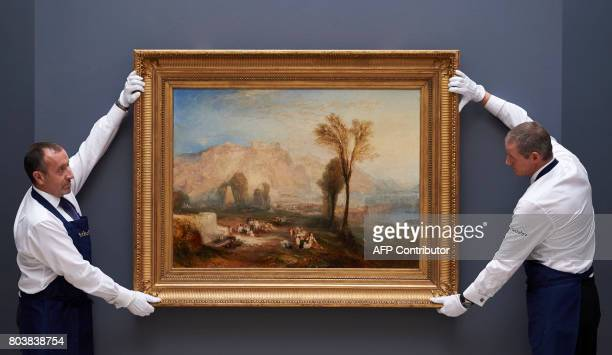 Employees of Sotheby's auction house pose with Ehrenbreitstein by British painter JMW Turner during a photocall to promote the forthcoming sale at...