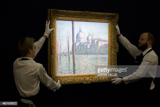 Employees of Sotherby's auction house position 'Le Grand Canal' by Claude Monet during a press preview in London on January 28 ahead of the...
