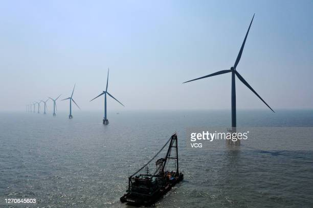 Employees of State Grid Corporation of China install a wind turbine at an offshore wind farm on September 3, 2020 in Zhoushan, Zhejiang Province of...