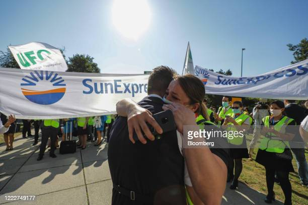 Employees of SunExpress a 5050 joint venture betweenDeutsche Lufthansa AGandTurkish Airlinesembrace during a protest outside the Lufthansa...