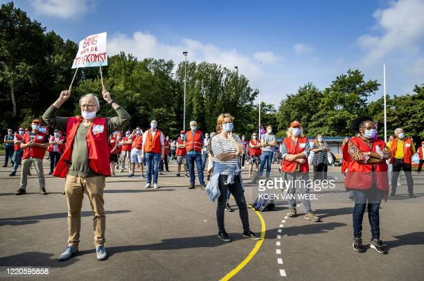 Employees of Tata Steel, wear protective face masks and stand at a distance as they strike against the impending reorganization and the departure of...