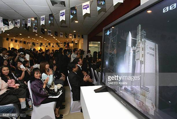 Employees of Thailand's private company Shin Satellite in Bangkok celebrate as a European Ariane 5 rocket lifted the world's largestever...