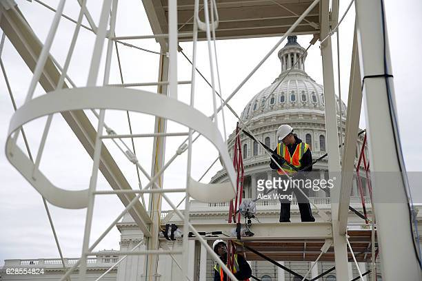 Employees of the Architect of the Capitol build a scaffolding at the West Front of the Capitol as construction of the 2017 presidential inaugural...