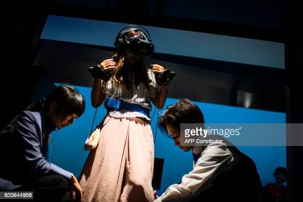 Employees of the Bandai Namco game company help a woman prepare to play a virtual reality Dragon Ball game at VR Zone Shinjuku in Tokyo on July 22...
