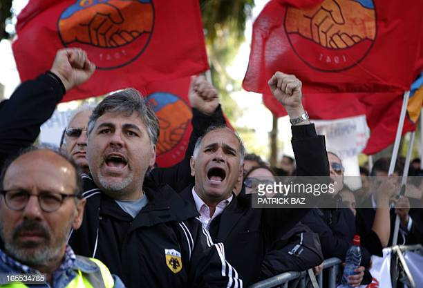 Employees of the bank shout slogans outside the parliament in the Cypriot capital Nicosia on April 4 during a demonstration over fears that pensions...