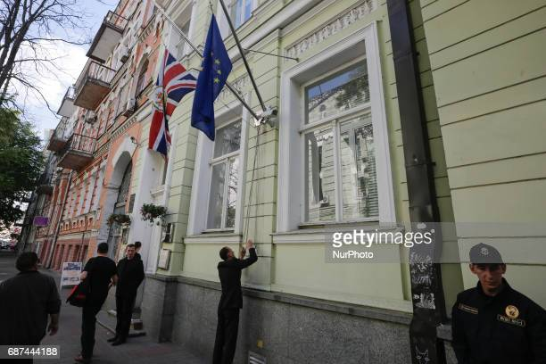 Employees of the British Embassy in Kiev, Ukraine fly a flag at half-mast, Tuesday, May 23, 2017. An apparent suicide bomber attacked an Ariana...