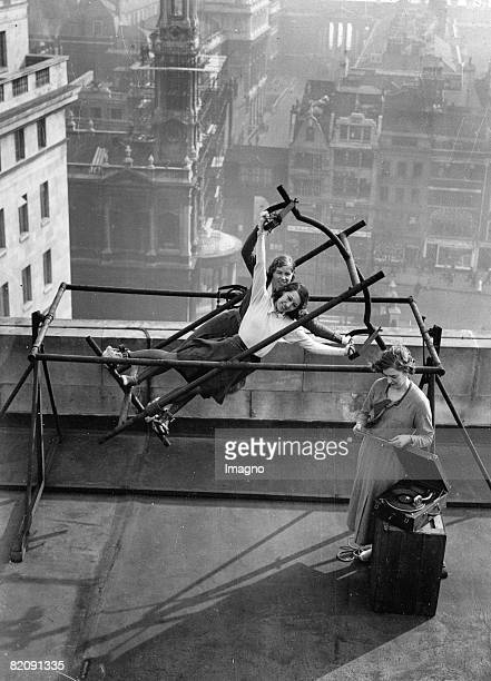 Employees of the Bush House Londons biggest office building at their lunch break on a new sports equipment Music from a gramophone is playing while...