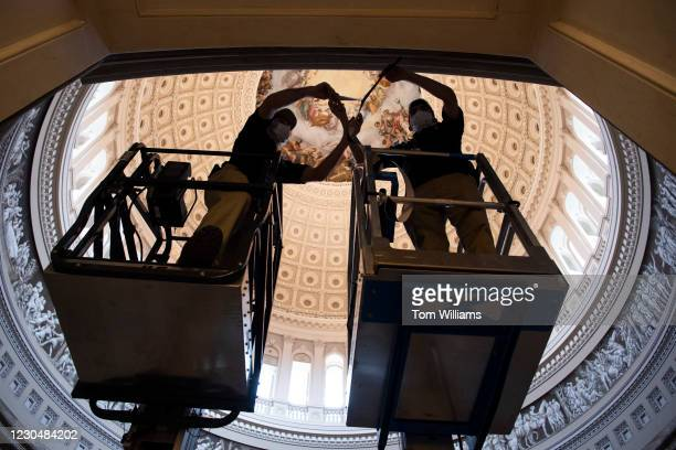 Employees of the Chief Administrative Office make preparations to hang drapes in the Capitol Rotunda for the upcoming presidential inauguration on...