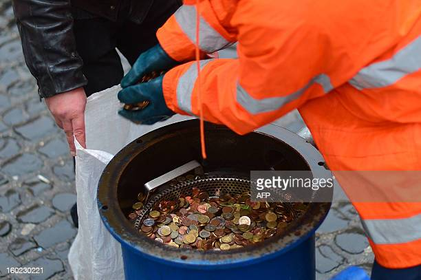 Employees of the city of Rome take coins from a vaccum cleaner used at the Trevi fountain on January 28 2013 in Rome A traditional legend says that...
