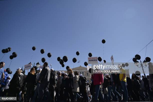 TOPSHOT Employees of The Ethniki Hellenic General Insurance Company an insurance Greek company hold black balloons and placards as they rally in...