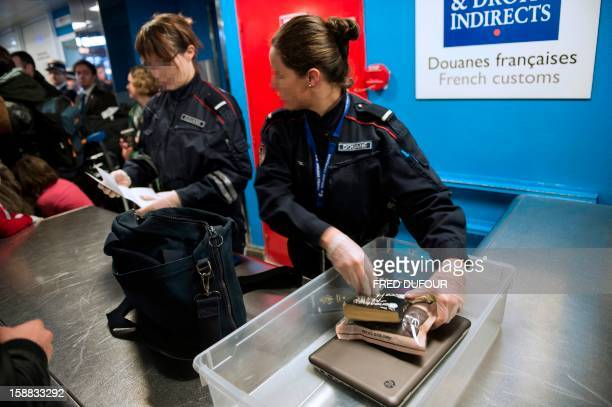 Employees of the French customs control luggages at the Charles de Gaulle airport on December 31 2012 in Roissy AFP PHOTO FRED DUFOUR / AFP PHOTO /...