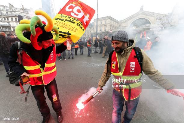 Employees of the French state owned railway company SNCF holding a flare demonstrate in front of the Gare de lEst railway station in Paris on March...