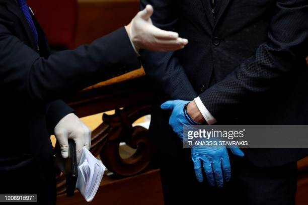 Employees of the Greek Parliament wearing plastic gloves attend the swearing-in ceremony of newly elected Greek President at the Greek Parliament in...