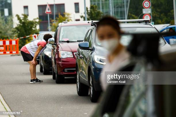 Employees of the health department instruct drivers about the Moderna vaccine in a drive-in vaccination station in an IKEA car park on the third day...