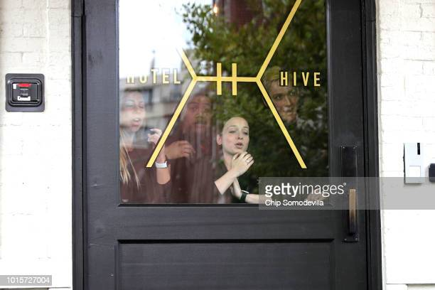 Employees of the Hotel Hive look out the front door as white supremacists with the Unite the Right rally march past on their way to White House...