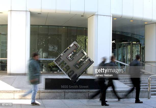 Employees of the Houstonbased energy trading firm Enron walk past the company's logo outside the corporate headquarters November 29 2001 in Houston...