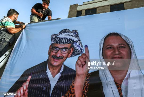 Employees of the Independent High elections and Referendum Commission of the northern Iraqi Kurdistan autonomous region hang up posters encouraging...