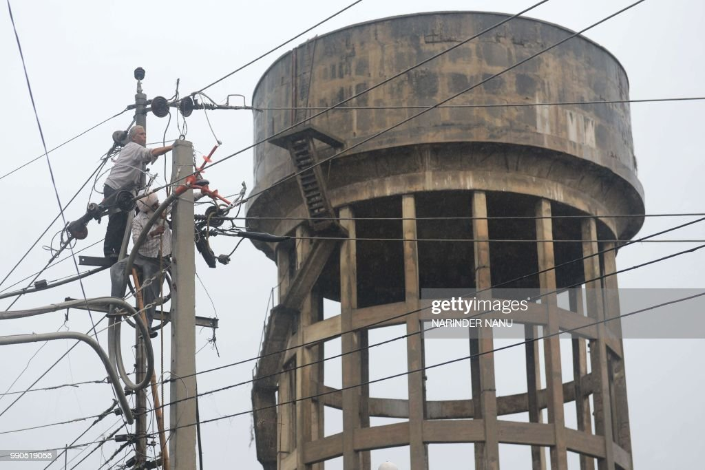 Employees of the Indian Punjab State Power Corporation Limited carry on repair works on the electrical network during heavy rain showers in Amritsar..