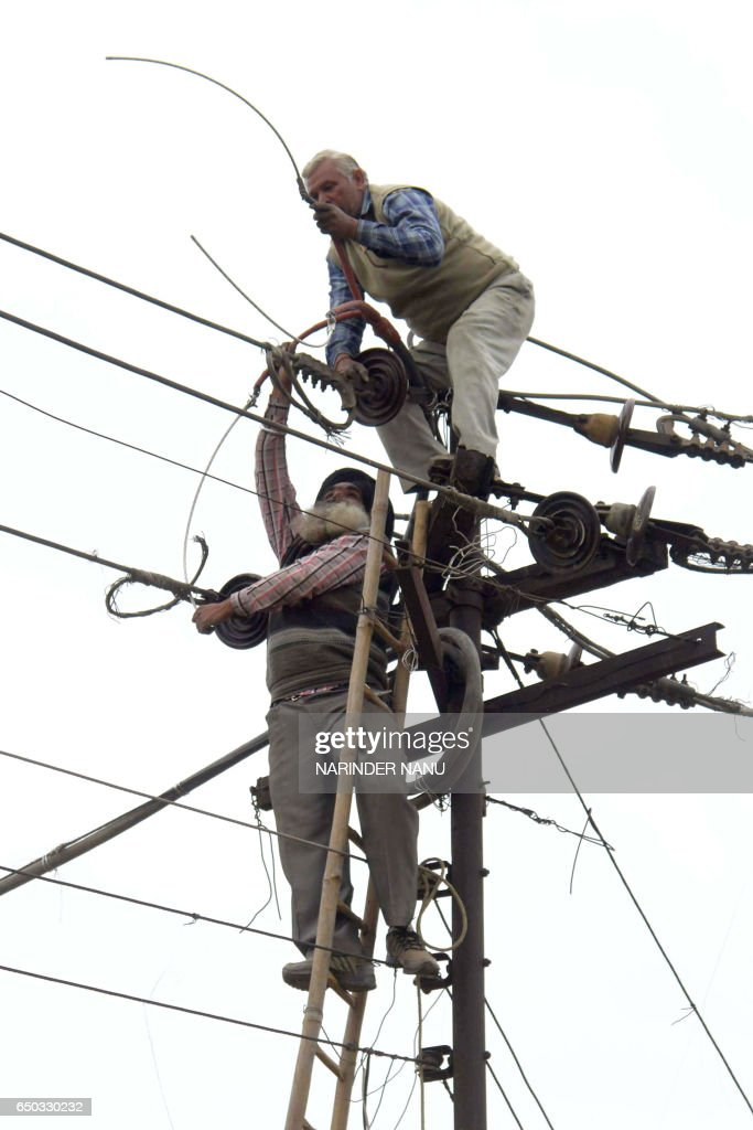 Employees of the Indian Punjab State Power Corporation Limited repair electrical wires in Amritsar on March 9 2017 / AFP PHOTO / NARINDER NANU