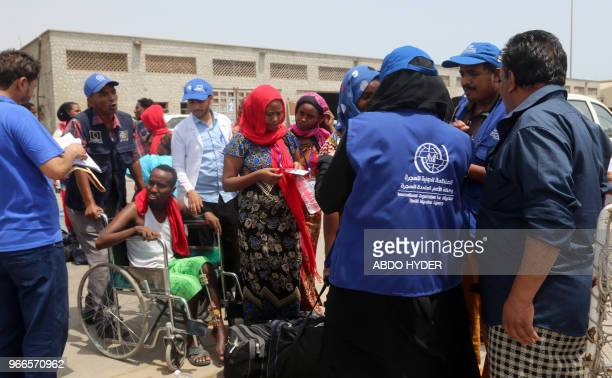Employees of the International Organisation for Migration assist Ethiopian migrants to board a ship repatriating them home via Djibouti in Yemen's...
