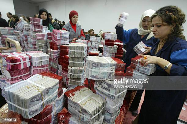Employees of the Iraqi Central Bank stack wads of old banknotes stained withg red ink with the picture of ousted leader Saddam Hussein in Baghdad 15...