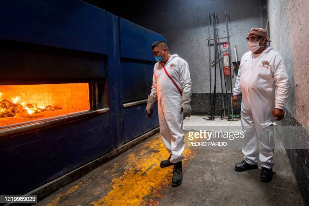 Employees of the Iztapalapa pantheon observe during the cremation of a victim of COVID-19 in Mexico City, on June 11 amid the novel coronavirus...