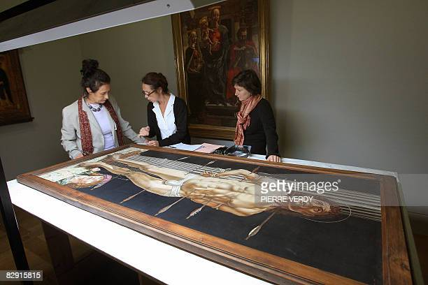Employees of the Louvre museum look at a painting by Italian Renaissance artist Andrea Mantegna on September 19 2008 at the Louvre museum in Paris...