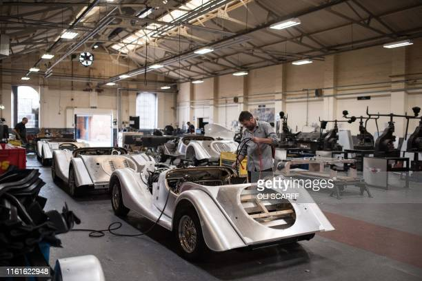 Employees of The Morgan Motor Company work in the assembly bay at the car firm's factory in Malvern southwest of Birmingham central England on August...