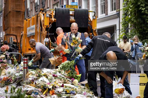 Employees of the municipality are cleaning up the flowers and cards that have been placed by mourners as a tribute for Peter R. De Vries in the Lange...