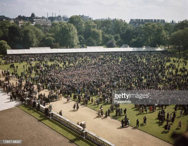 Employees of the National Savings Bank congregate on the lawn for a Royal Garden Party in the grounds of Buckingham Palace in London in July 1946.