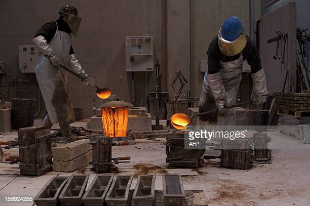 Employees of the Noack foundry pour melted silicon bronze into a mould to cast the Golden Bear trophy for the upcoming Berlinale Film Festival in...