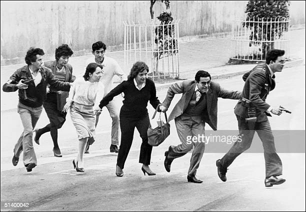 Employees of the Palace of Justice in Bogota leave their office 06 November 1985 under police protection after a M19 movement guerrillas commando...