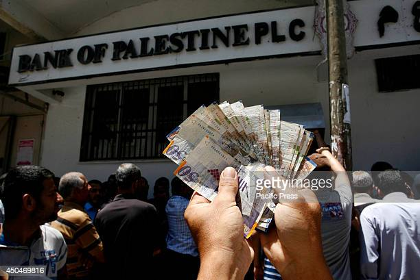 Employees of the Palestinian National Authority withdrawing cash from an Automated Teller Machine in Rafah in the southern Gaza Strip Palestinian...