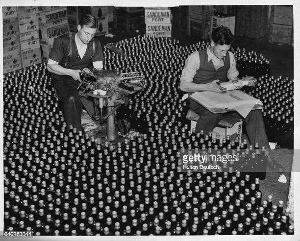 Employees of the Port of London Authority label and pack bottles of port | Location Port of London Authority warehouse London England