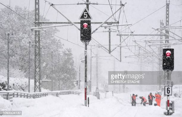 TOPSHOT Employees of the railway clear the tracks from snow during heavy snowfall near the railway station in Mittenwald near GarmischPartenkirchen...