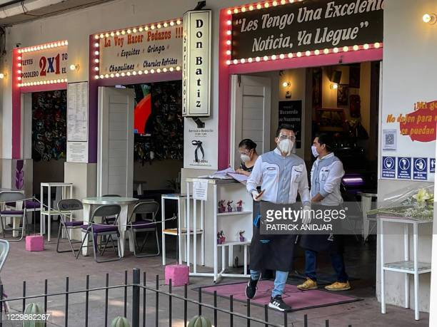 Employees of the restaurant owned by French businessman Baptiste Jacques Daniel Lormand, put flowers and candles at the restaurant's entrance, after...