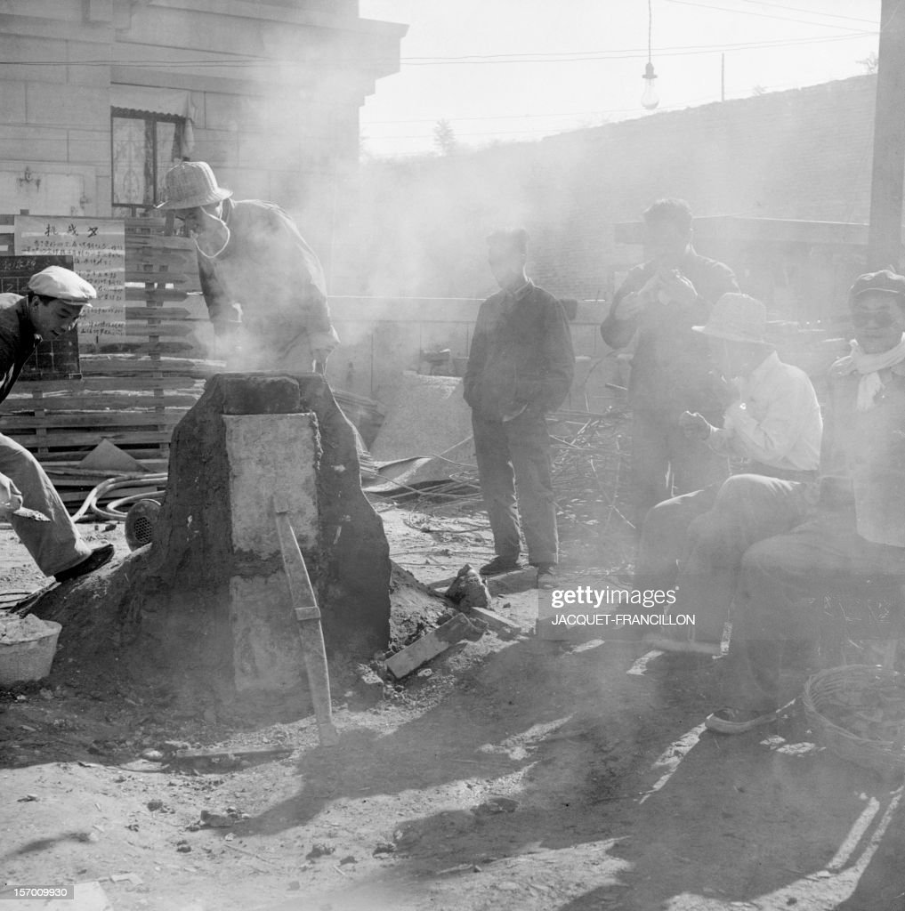 Employees of the Shin Chiao Hotel in Beijing build in the hotel courtyard (background) in October 1958 a small and rudimentary smelting steel furnace during the period of the 'Great Leap Forward' (1958-1959), which was due to mobilize the Chinese population and to emphasize local authority and establish rural communes.
