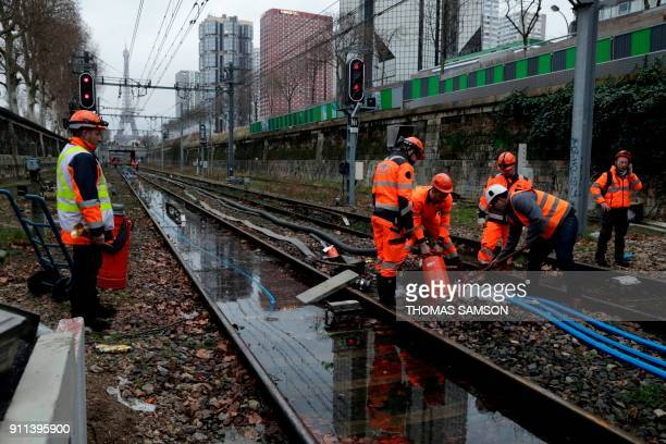 Employees of the SNCF France's stateowned railway company are at work to pump water out of the flooded railroad of the Javel RER C station on January...