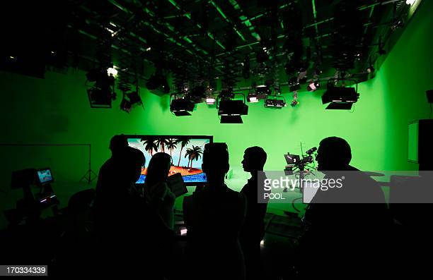 Employees of the stateowned Englishlanguage Russia Today television network are silhouetted against the backdrop as they wait for the arrival of...
