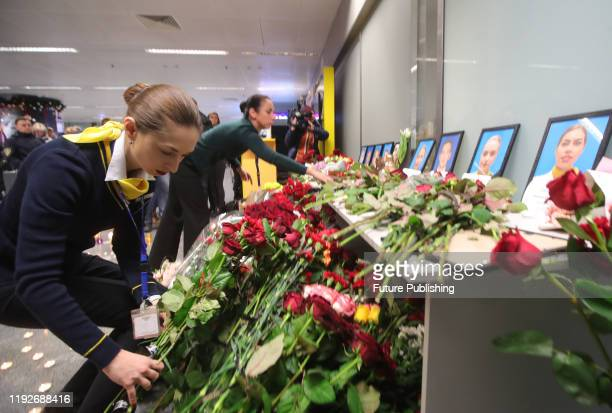 Employees of the Ukraine International Airlines arrange flowers at the portraits of nine crew members who were among 176 people on board of the UIA...
