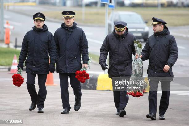 Employees of the Ukraine International Airlines carry bouquets as they head for a lying-in-repose ceremony to pay their last respects to nine of...