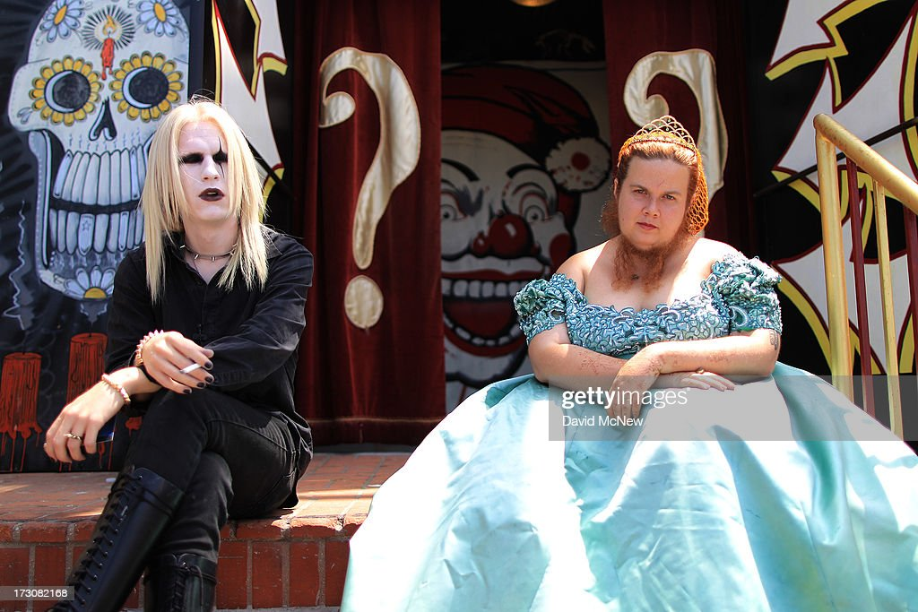 Employees of the Venice Beach Freakshow, Morgue (L) and Jesse the Bearded Lady, sit on the steps of the theater during a break on Independence Day weekend at Venice Beach on July 6, 2013 in Venice, California. An estimated 16 million people visit the famous beach city annually which is celebrating 108th birthday as of July 4.