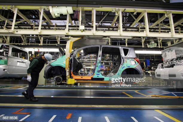 Employees of Toyota Motor Corporation work during the assembly process at the company's Takaoka Plant on December 2, 2005 in Toyota, Aichi...